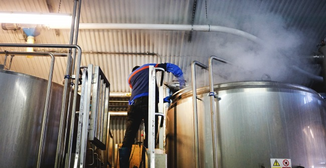 A brewer adds hops to the kettle at The Five Points brewery in Hackney, London