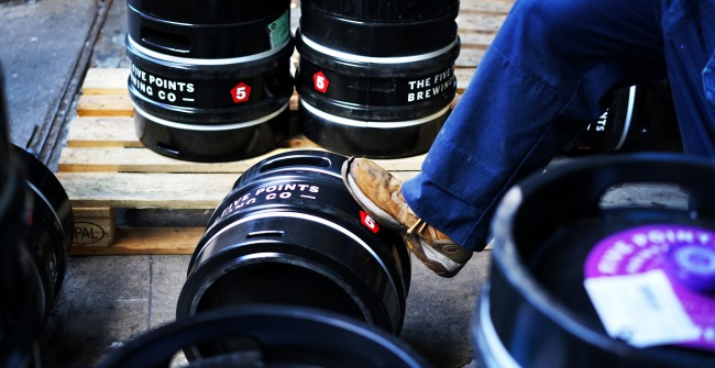 A brewer rolls a keg of Five Points beer in Hackney, London