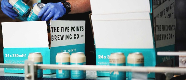 Brewery staff packaging cans of Five Points XPA into cases